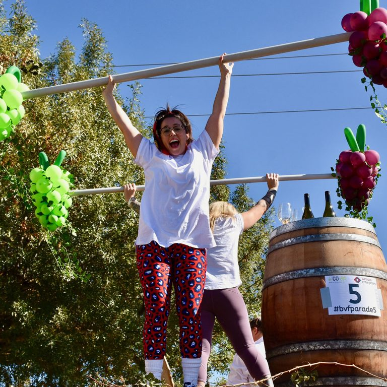 """Melanie Kaye, Barossa Exercise Physiology tests her abilities to """"pump some weights"""" as part of their float entry."""